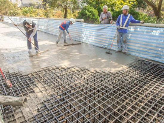 Construction of the pedestrian walkway in New Taipei City, Taiwan: the concrete pour takes place after all the Aqueduct Assembly structural grid units and gravel are laid in place. (Photo courtesy Ping Tai Co., Ltd.)